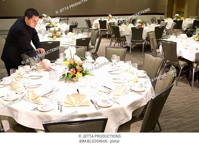 Pacific Islander waiter setting tables in dining room