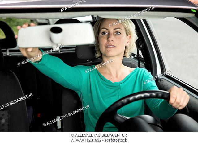 Female car driver is setting her car mirror