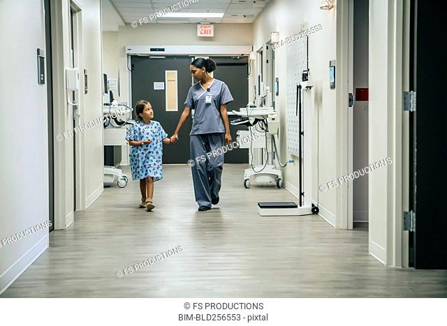 Nurse holding hands with girl in hospital