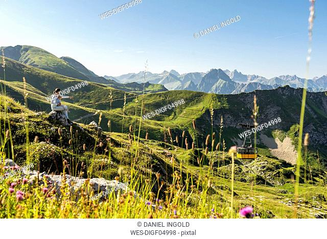 Germany, Bavaria, Oberstdorf, mother and little daughter on a hike in the mountains having a break looking at view