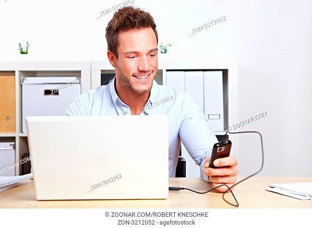 Junger Mann am Schreibtisch verbindet Handy mit Laptop im Büro