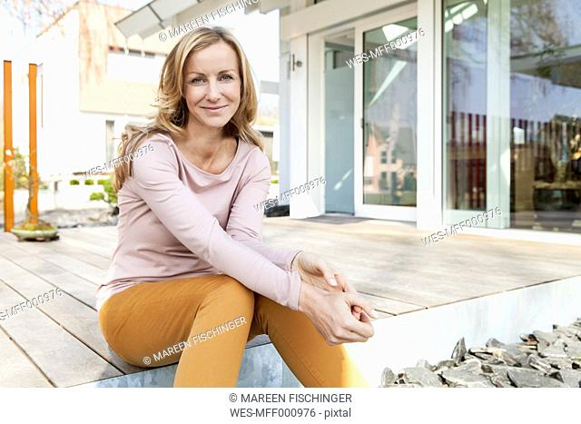 Smiling woman sitting on terrace of residential house