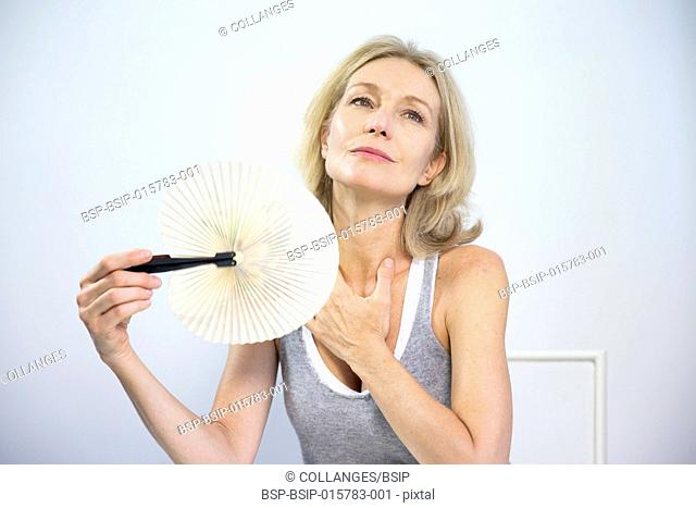 Woman fanning herself to relieve the symptoms of a hot flush