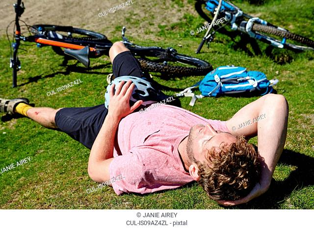 Cyclist lying down on grass by bicycle