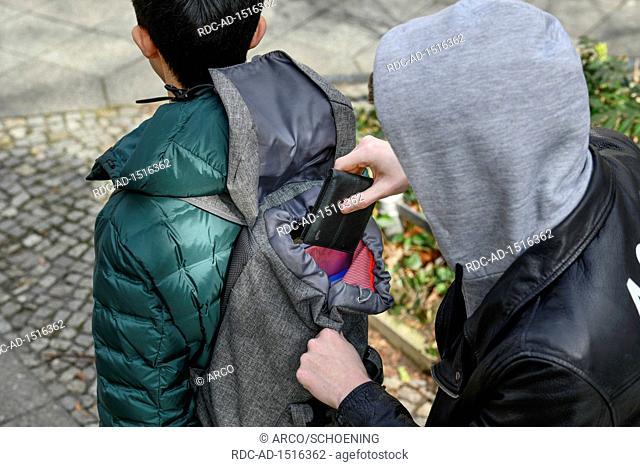 Diebstahl einer Geldboerse aus einem Rucksack, Strassenkriminalitaet, gestelltes Foto