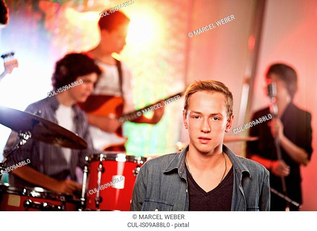 Teenage boy with band in background