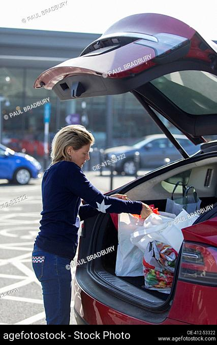 Woman loading groceries into back of car in parking lot