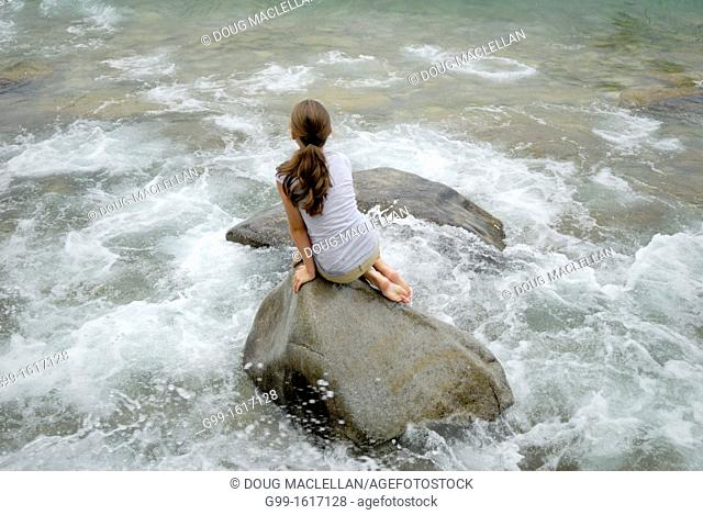 Nine year old girl sits on a large boulder and watches choppy waves, Barrow Bay, Ontario, Canada
