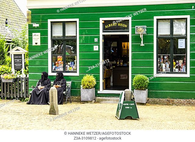 Two women in niqab chilling in front of the oldest Albert Heijn at the Zaanse Schans, North-Holland, the Netherlands, Europe