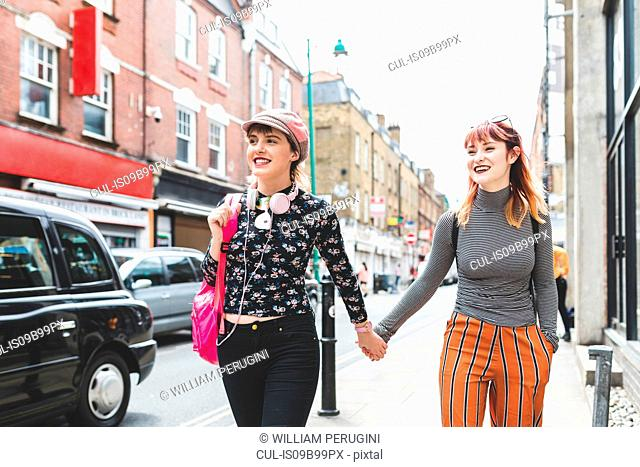Two retro styled young women strolling on city street holding hands