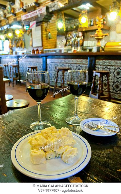Spanish appetizer: alioli potatoes with two glasses of red wine in a bar. Madrid, Spain