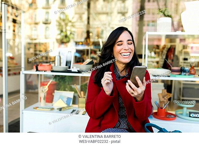 Happy woman using cell phone in front of shop window