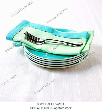 Napkin and dessert forks on stack of plates