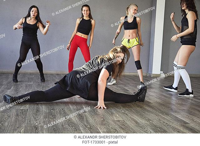 Young woman doing splits while friends dancing at studio