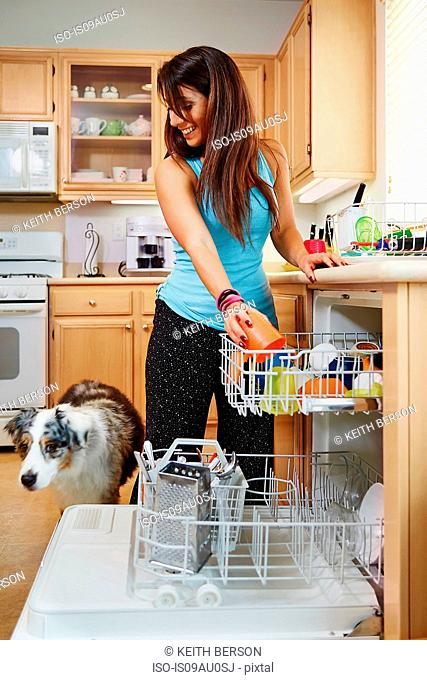 Woman loading dishwasher, dog beside her