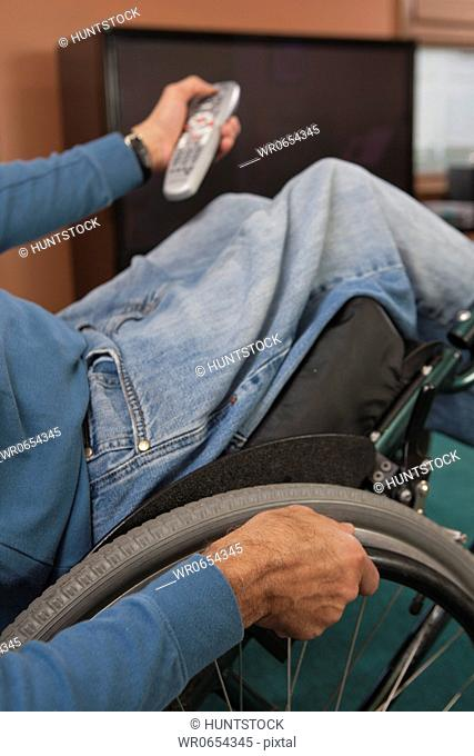 Man with spinal cord injury in a wheelchair using a remote control