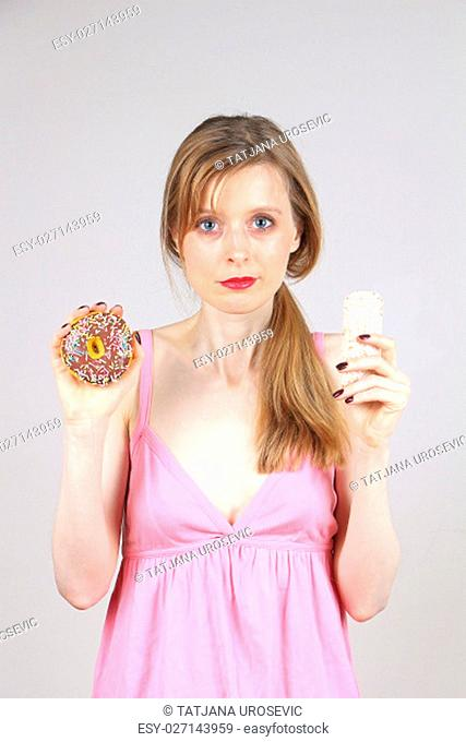 Woman holding donut and rice cake in her hands giving you a choice