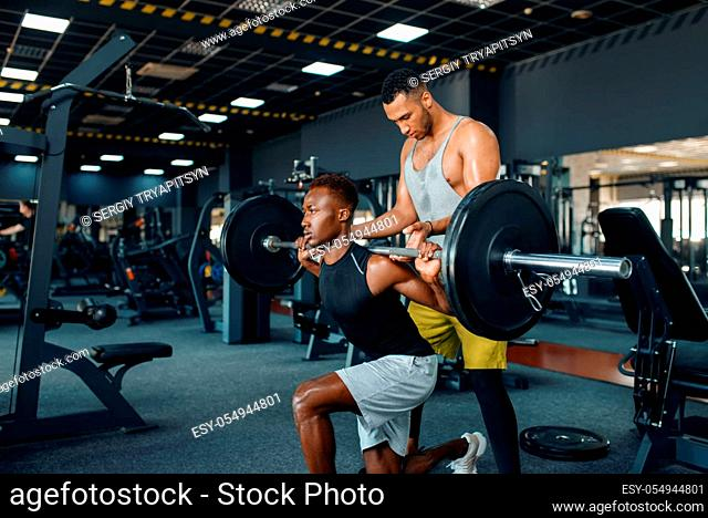 Trainer helps the athlete, exercise with barbell on training in gym. Workout in sport club, healthy lifestyle