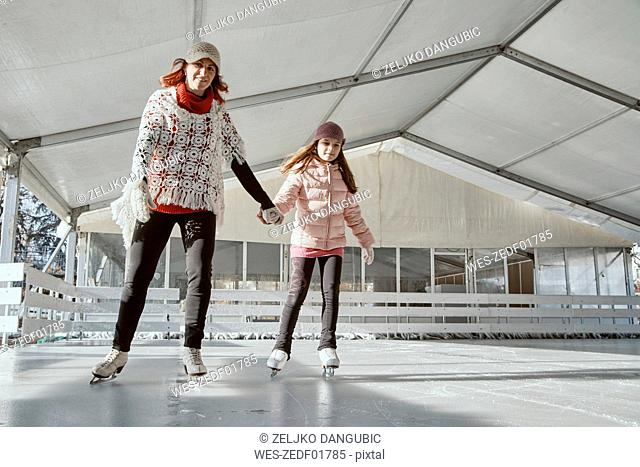 Mother holding hand of her daughter , while ice skating