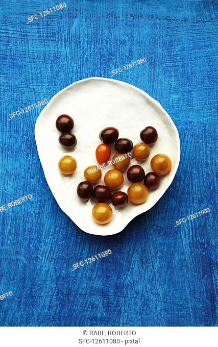 Various cocktail tomatoes on a plate against a blue background