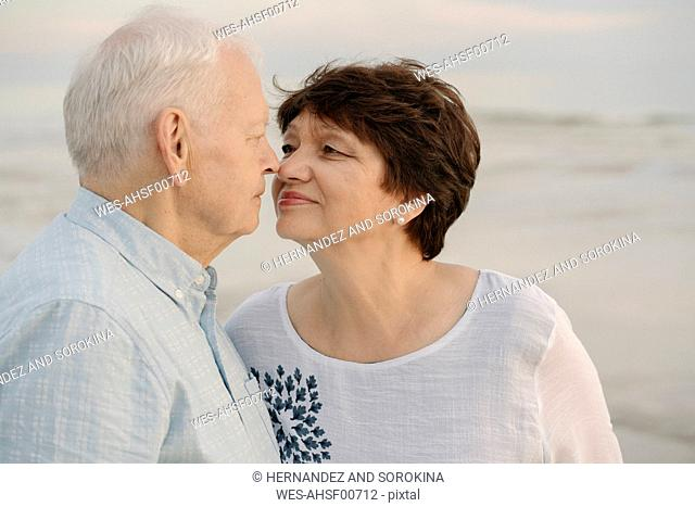 Senior couple rubbing noses in front of the sea, Liepaja, Latvia