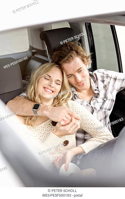 Young couple in love sitting in the car holding hands
