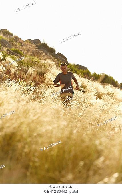 Man running through tall sunny grass