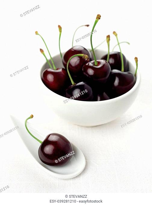 Single cherry on a white china spoon and a ripe group cherries in a small round white bowl