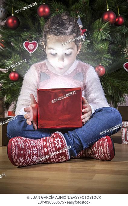 Little girl opening her present under Christmas tree. She is illuminated by shine from box