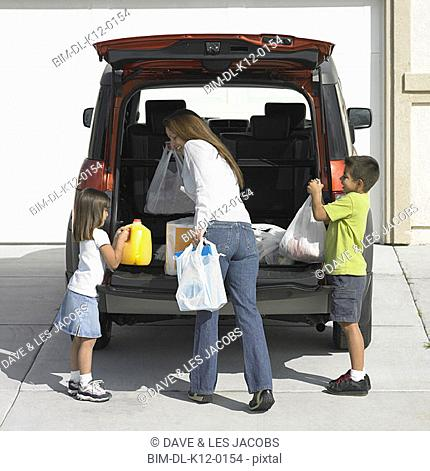 Mother and children carrying groceries from van