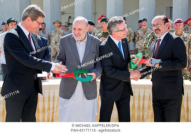 Defense Minister Thomas de Maiziere (2-R) hands over a symbolic key to Deputy Secretary of Defense Nasrulla Nasary (R) while Foreign Minister Guido Westerwelle...