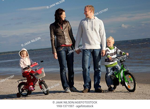 Happy Young Family Holding Hands Walking with Kids on Bicycles by Sea, Pärnu Beach, Estonia