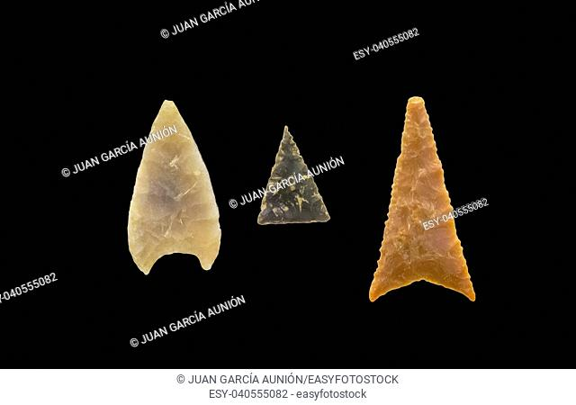 Three late bronze period stone arrow heads. Isolated over black