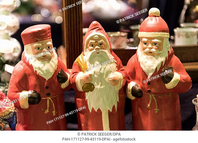 Three figures of Father Christmas are displayed at a stand at the Christmas market in Freiburg, Germany, 27 November 2017