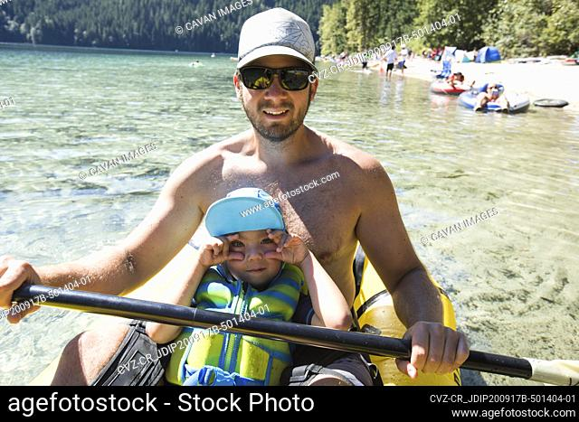 Father and son enjoying a beach day in their inflatable kayak