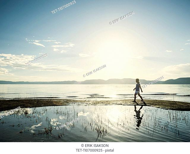 Small girl (4-5) walking on sand on sunny day