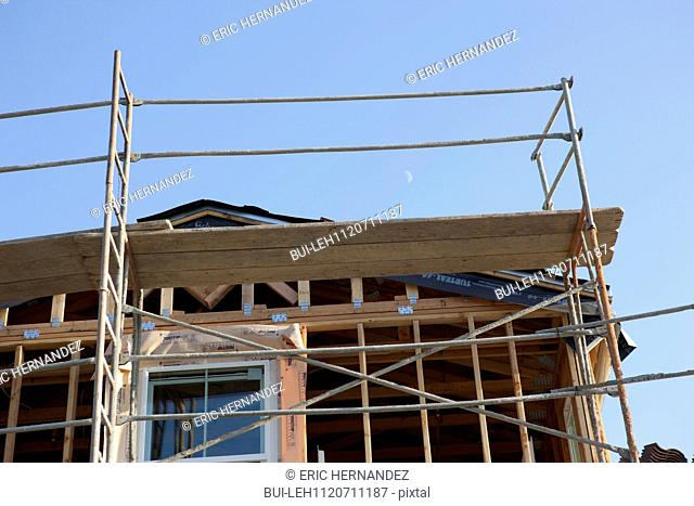 Low angle view of house under construction against clear sky; Azusa; California; USA