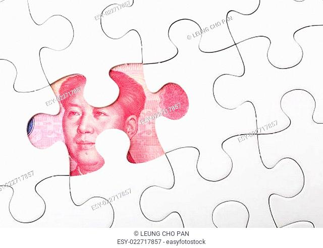 White puzzle and chinese banknote