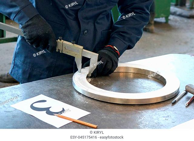 The worker, the engineer measures the part, the shiny metal ring, the flange with a caliper on the working iron table in the factory, the shop