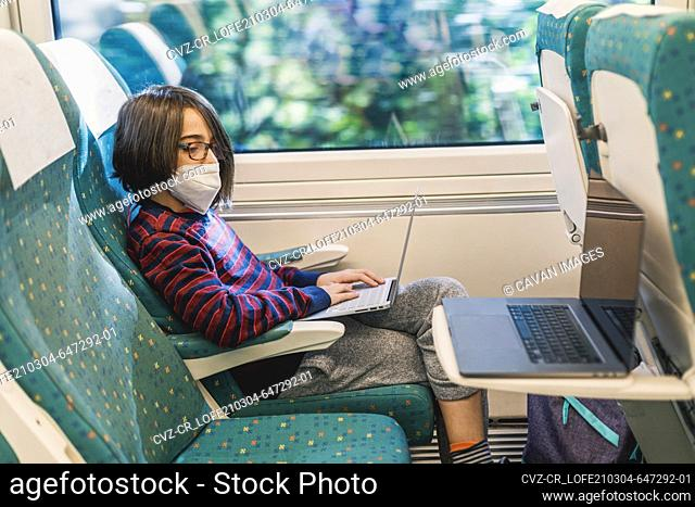 Two laptops and boy with mask uses computer while traveling by train