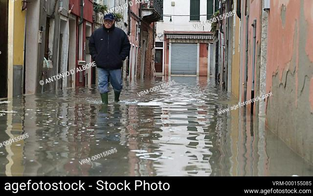 A local resident walking in an alley in Castello Quarter, during during the so called 'acqua alta' high tide. Venezia. Italy