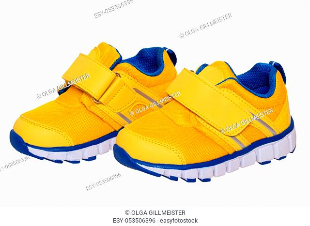 Child shoe fashion. Close-up of a pair of yellow blue child sneaker or sport shoes isolated on a white background. Elegant and trendy shoes for girls