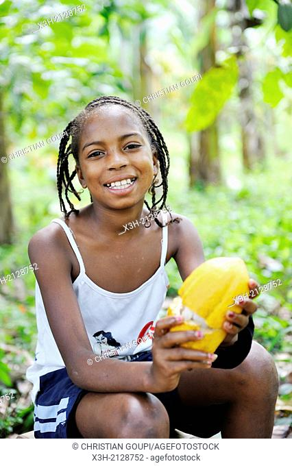 teenager holding a cocoa pod in a plantation around the village of Praia das Conchas, in the northern part of Sao Tome Island, Republic of Sao Tome and Principe
