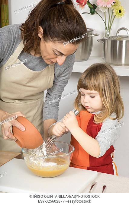 woman pouring flour in glass bowl, and three years old child whipping with whisk, in teamwork, making and cooking a sponge cake at kitchen home,