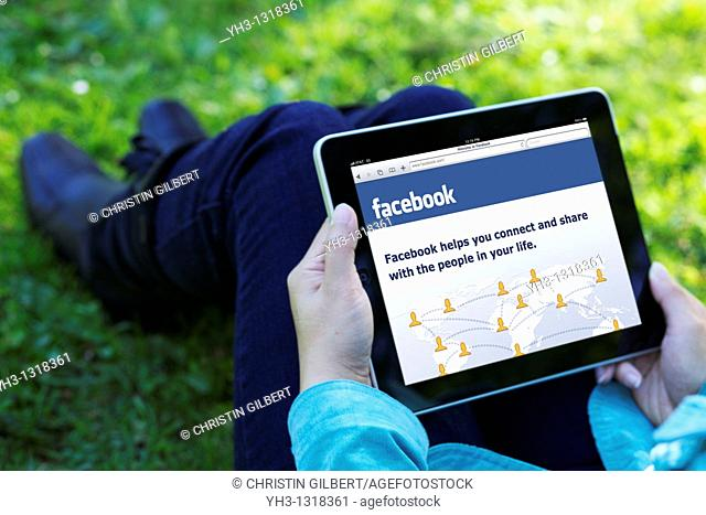 A woman hand holding an iPad while showing Facebook screen