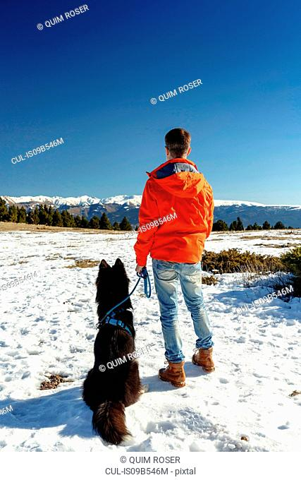 Rear view of man with dog looking out at snow covered landscape