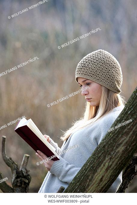 Austria, Mondsee, portrait of reading teenage girl in autumn