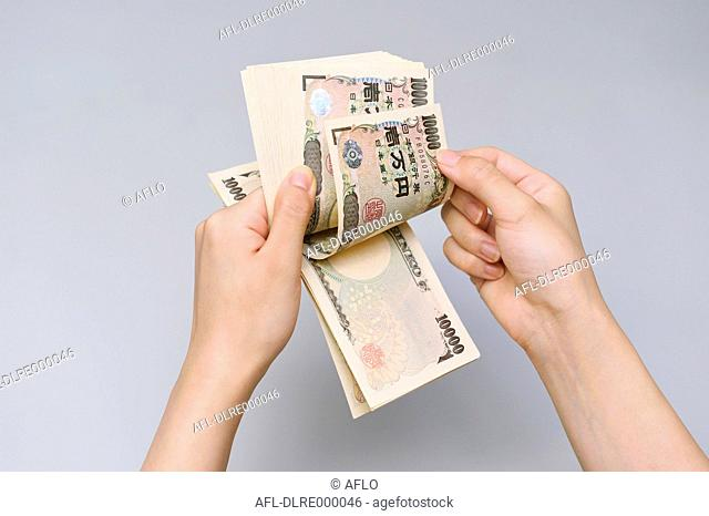 Woman hands counting ten thousands Japanese Yen bills