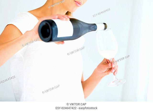 Gorgeous young woman with a glass of wine, pouring herself a glass of wine (shallow DOF color toned image)