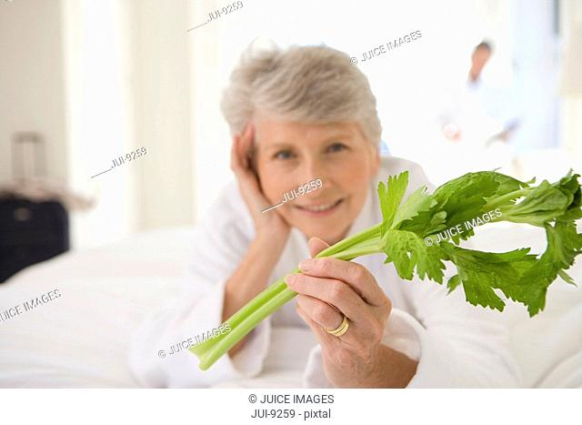 Senior woman lying on bed holding celery stick, smiling, portrait, close-up